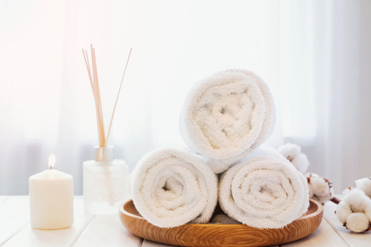 Clean white towels on the wooden tray, candle and aroma diffuser.