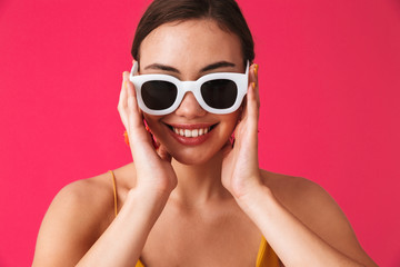 Photo closeup of european cheerful woman 20s wearing fashion earrings and glasses smiling at you, isolated over pink background
