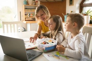 Mother helping children with homework in kitchen