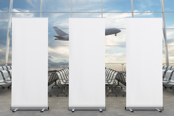 Blank roll up banner stands and airplane on background in airport terminal lounge. Include clipping path around ad poster. 3d render