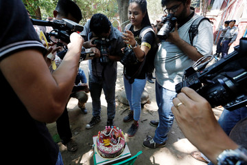 Reporters and friends of Wa Lone take photos of Wa LoneÕs birthday cake outside of Insein court room in Yangon