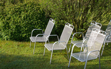Metallic silver chairs in park on grass