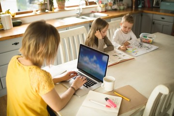 Siblings drawing while mother working on laptop in kitchen