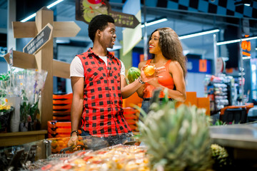 African couple shopping in supermarket produce department