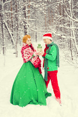 young couple, man and woman, husband and wife are walking in costumes of flowers typical of the elves of Santa's helpers in a winter forest under the snow with a chest full of gifts and a giant candy