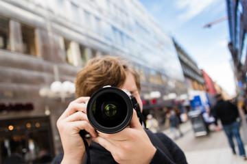 Young man tourist taking photo at street