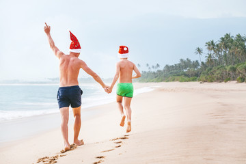 Father and son in Santa's hats run on perfect sand beach on tropical island. Christamas and New Year holiday vacation