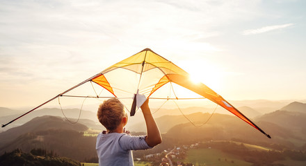 Boy starts to fly a kite over the mountain hills at sunset time