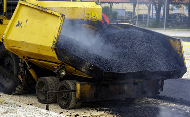 Asphalt paver with asphalt heated to temperatures above 160 ° during road at the construction
