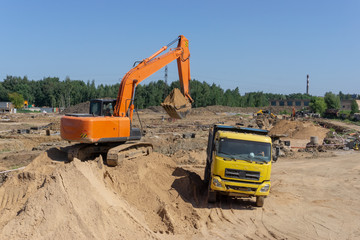 Excavator at the construction site will load the truck with sand