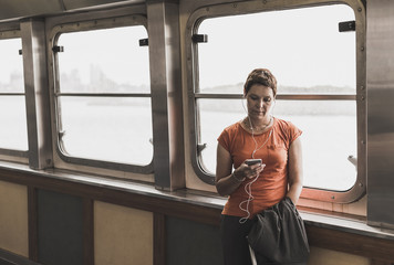 Woman on a ferry looking on cell phone