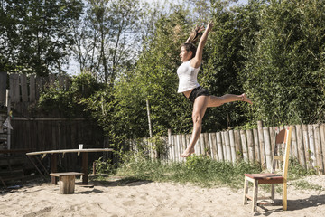Young woman jumping in the air outdoors