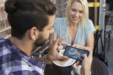 Young man with girlfriend taking cell phone picture at outdoor cafe