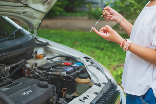 Woman's hand checking automobiles engine oil level on the dipstick for transportation and vehicle concept