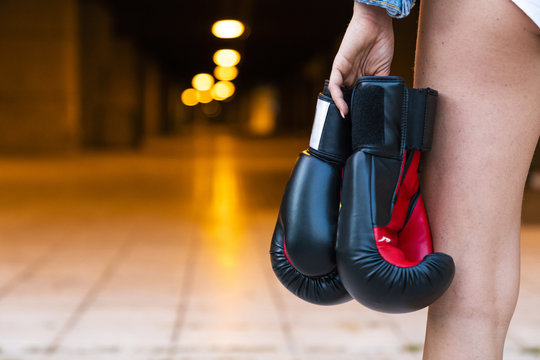 Close-up of woman holding boxing gloves at illuminated underpass