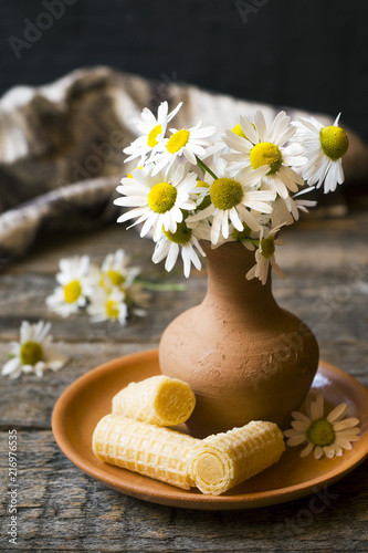 Still Life Of A Bouquet Of Daisies In A Vase And Waffle Tubes