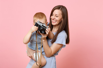 Portrait of happy family. Mother keep in arms, have fun, hug son baby boy, take picture on retro vintage photo camera on pink background. Sincere emotions, Mother's Day, parenthood, childhood concept.