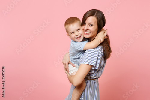 Portrait happy young family. Mother keep in arms, tender embrace, gently hugs child kid son baby boy on pastel pink background. Sincere emotions, fondness, Mother's Day, parenthood, childhood concept.