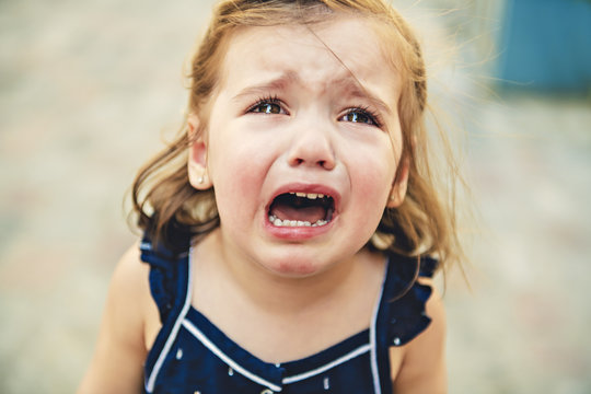 Close up portrait of crying little toddler girl with outdoors background. Child