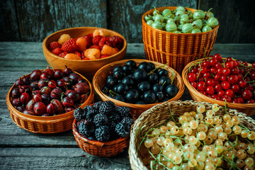 Close up different kind of baskets with fruits on vintage wood background. Red, black and white currant, green and red gooseberry, blackberry and raspberries.