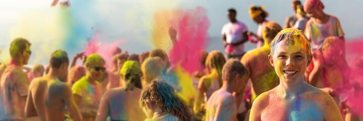 Breitbild - Holi Fest begeisterte Menschen jubeln auf einem Holifestival, tanzen und werfen mit buntem Holipulver, Junge lacht in die Kamera