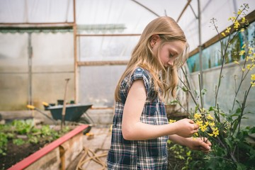 Girl holding flower in hand at greenhouse