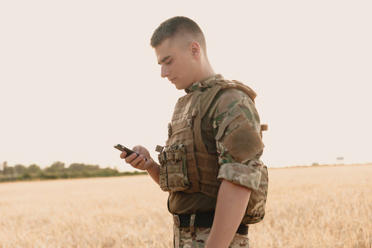 Mid section of military soldier using mobile phone in boot camp. letter from war.