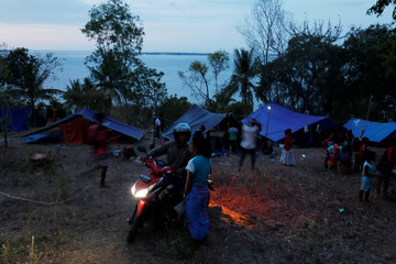 Villagers worried about earthquake aftershock and tsunami make a temporary shelter at an empty resort atop a hill in Senggigi beach