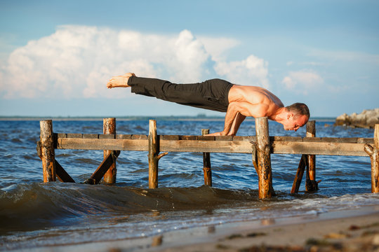 Young yoga trainer practicing mayurasana or peacock pose on a wooden pier on a sea or river shore.