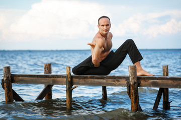 Young yoga trainer practicing yoga exercises on a wooden pier on a sea or river shore