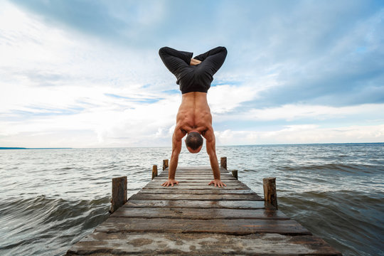 Young yoga trainer practicing handstand with a lotus on a wooden pier on a sea or river shore.