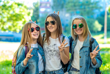 Three girls schoolgirl teenager, wearing jeans clothes and sunglasses. Happy smiling with gesture of hands showing Hello. Emotions of happiness and relaxation. The concept is best school friends.