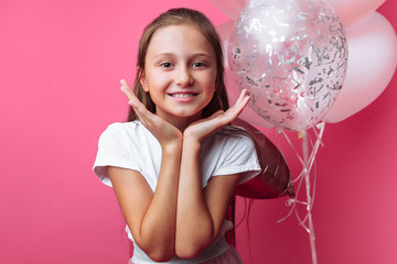 portrait of a girl with balloons in the Studio, on a pink background, close-up