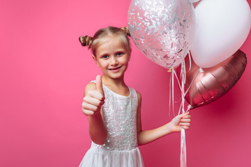 portrait of a little girl with balls, on a pink background in a photo Studio, close-up