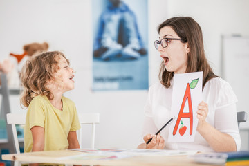 Speech therapist working with a child on a correct pronunciation using a prop with a letter 'a' picture.