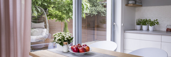 Real photo of fresh apples on plate placed on wooden dining table standing in bright kitchen interior with glass door to terrace and countertop with plants