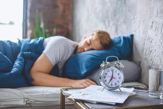 selective focus of alarm clock and sleeping man in bed behind