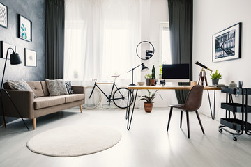 Modern home office interior with a big window, sofa, bike and desk with a computer. Place your product