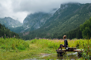 Side view shot of young woman sitting on the wooden dock on small pond with beautiful view of green hills and rocky peaks of Rysy mountains, Tatra. Poland and Slovakia