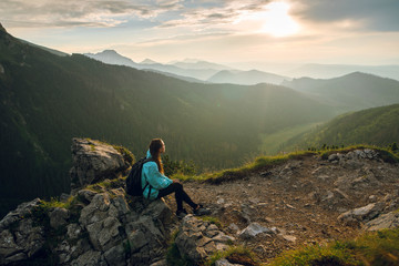 Side view shot of beautiful young woman in blue jacket, with backpack sitting on the rocks on the Rysy mountain peak in Tatras, Slovakia and Poland. Beautiful sunset