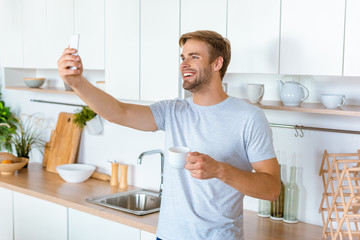 handsome smiling man with coffee cup taking selfie on smartphone at kitchen