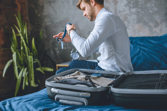 selective focus of businessman packing luggage in suitcase in bedroom at home