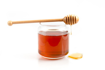 Jar of honey and a wooden dipper on white isolated background