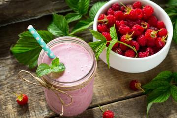 Raspberry milkshake or smoothie on a white wooden background. Healthy juicy vitamin drink diet or vegan food concept.