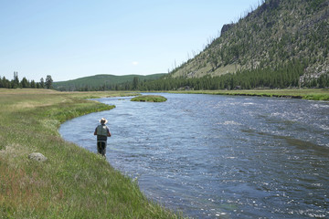 Fisherman flyfishing in river of Montana state