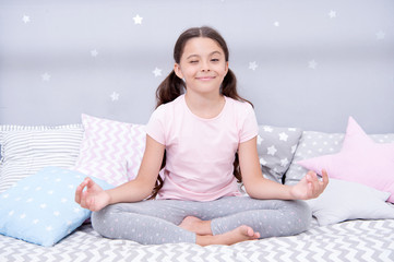 Meditate before go to bed. Girl child sit on bed in her bedroom. Kid prepare to go to bed. Pleasant time for evening meditation. Girl kid long hair cute pajamas relaxing and meditating in bedroom