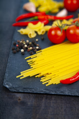 Different pasta on a wooden background.