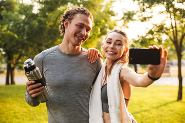Fitness sport loving couple holding bottle with water.