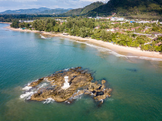 Aerial drone view of a small offshore lighthouse next to a tropical beach and mountains (Khao Lak, Thailand)