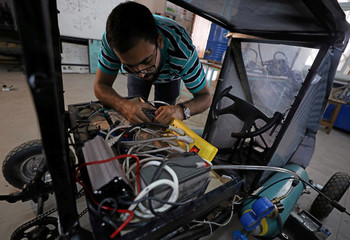 Islam Ibrahim, mechanical engineering student from Helwan University, checks electrical cables on the air-powered vehicle which he helped design to promote clean energy and battle increasing gas prices, in Cairo